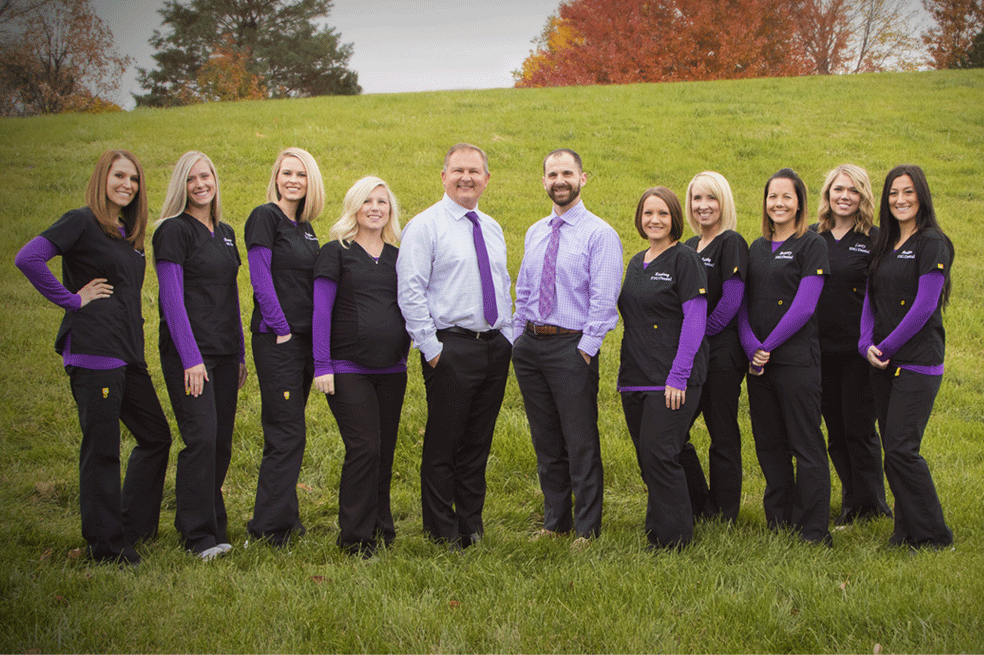Dental-staff-and-dentists-posed-outside-with-purple-and-black-dental-uniforms-on