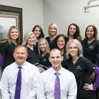 dentists and dental staff in patient room wear black and purple