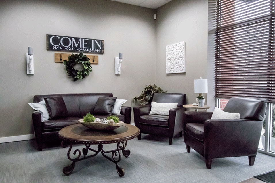 Brown leather arm chairs and soft in patient waiting area of SYGD dentist office