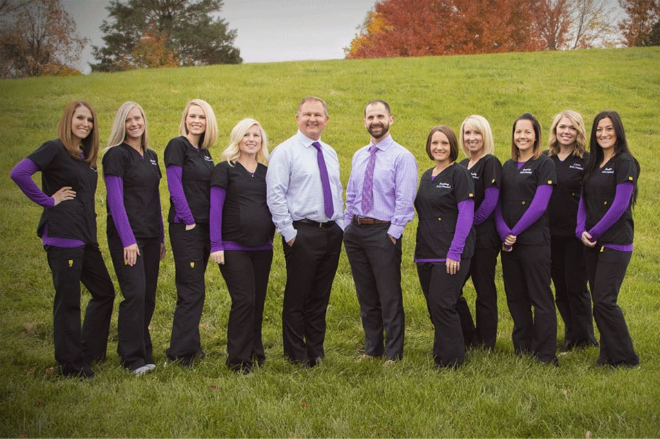 Dental staff and dentists posed outside with purple and black dental uniforms on.