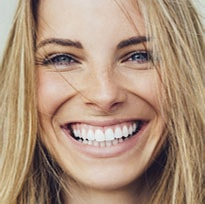 Close up of woman with blonde hair smiling with great looking and healthy gums.