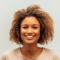 woman with large hair smiling and showing straight white teeth from cosmetic dentistry treatment