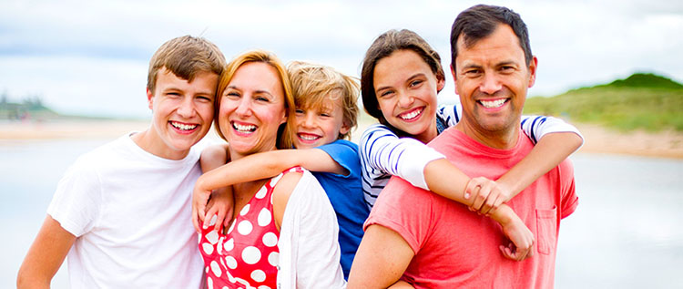 A family of dentist patients wearing bright colored short-sleeve shirts on vacations and smiling, showing white teeth.